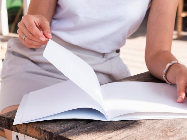 Nahaufnahmefrau, die eine modellzeitschrift liest Kostenlose Fotos
