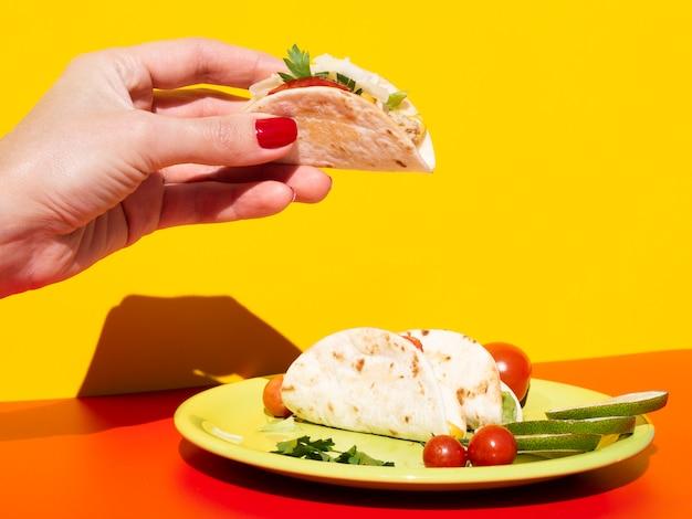 Nahaufnahmefrau, die geschmackvollen taco hält Kostenlose Fotos