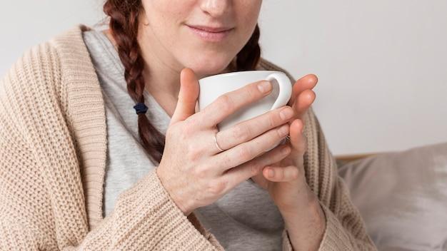 Nahaufnahmefrau, die heißen tee trinkt Kostenlose Fotos