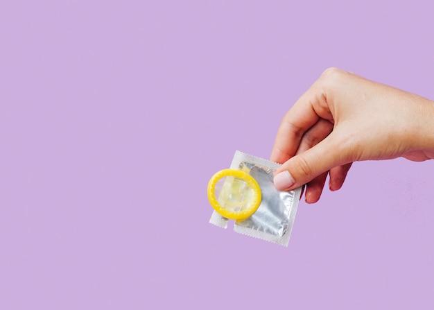 Nahaufnahmefrau, die kondom mit kopieraum hält Kostenlose Fotos