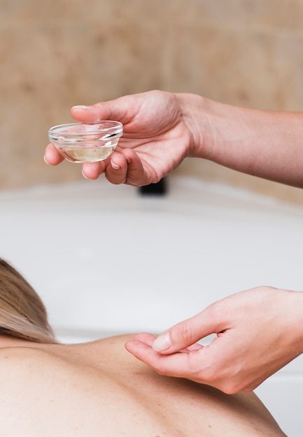 Nahaufnahmefrau, die kunden mit badekurortöl behandelt Kostenlose Fotos