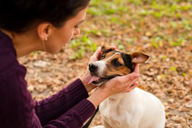 Nahaufnahmefrau, die mit ihrem hund spielt Kostenlose Fotos