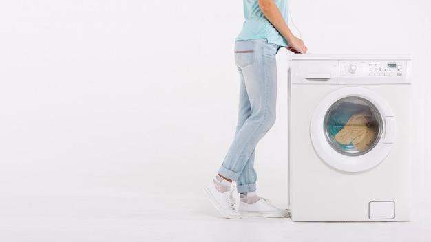 Nahaufnahmefrau, die nahe waschmaschine sitzt Kostenlose Fotos
