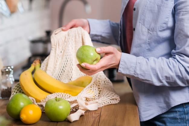 Nahaufnahmefrau, die organische früchte aus der öko-tasche erhält Kostenlose Fotos