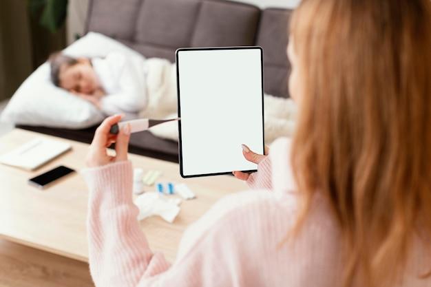 Nahaufnahmefrau, die tablette und thermometer hält Kostenlose Fotos