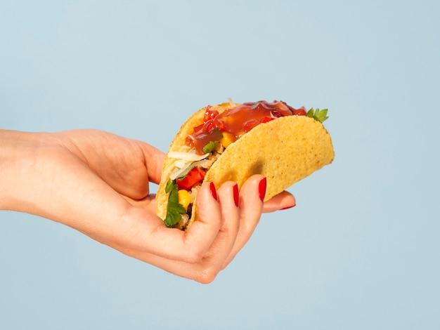 Nahaufnahmefrau, die taco mit blauem hintergrund hält Kostenlose Fotos