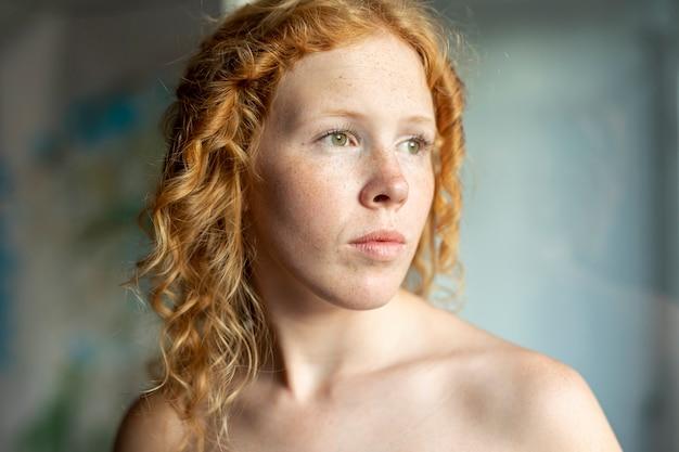 Nahaufnahmefrau, die weg schaut Kostenlose Fotos
