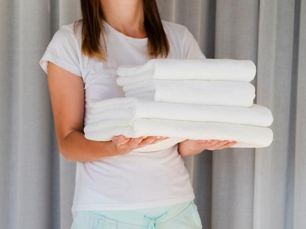 Nahaufnahmefrau, die weiß gefaltete saubere tücher hält Kostenlose Fotos