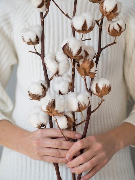 Nahaufnahmefrau, die zweige mit baumwollblumen hält Kostenlose Fotos