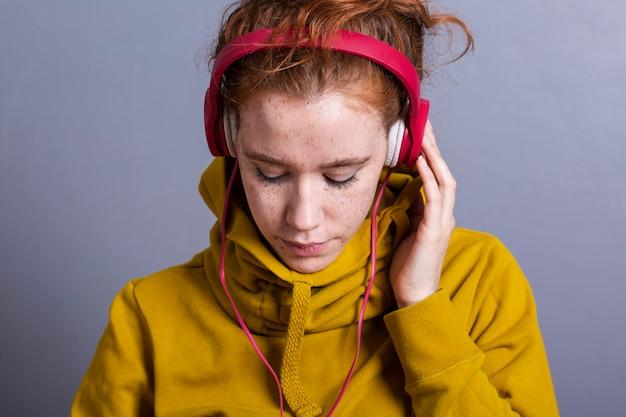 Nahaufnahmefrau mit gelbem hoodie und kopfhörern Kostenlose Fotos