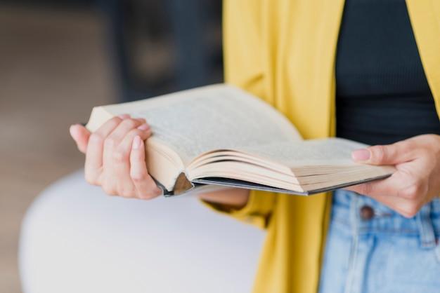 Nahaufnahmefrau mit gelber bluse und buch Premium Fotos