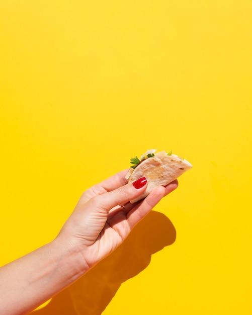 Nahaufnahmefrau mit taco und gelbem hintergrund Kostenlose Fotos