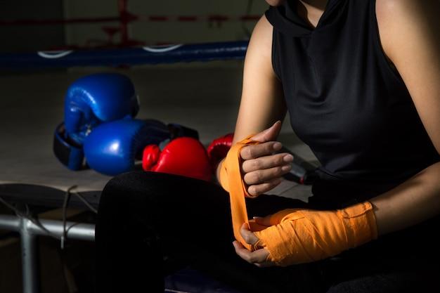 Nahaufnahmefrauen-boxerhand beim tragen des orange bügels auf handgelenk Premium Fotos