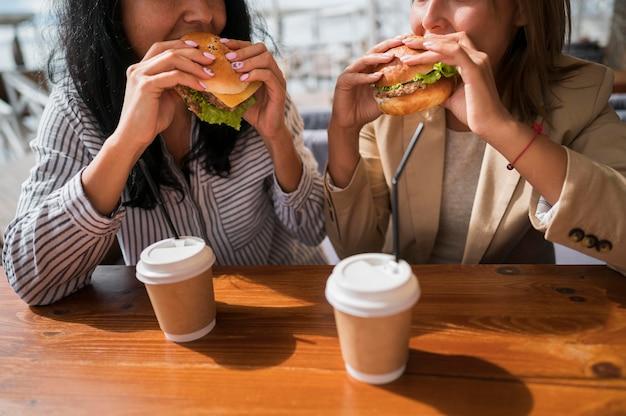 Nahaufnahmefrauen, die burger essen Kostenlose Fotos