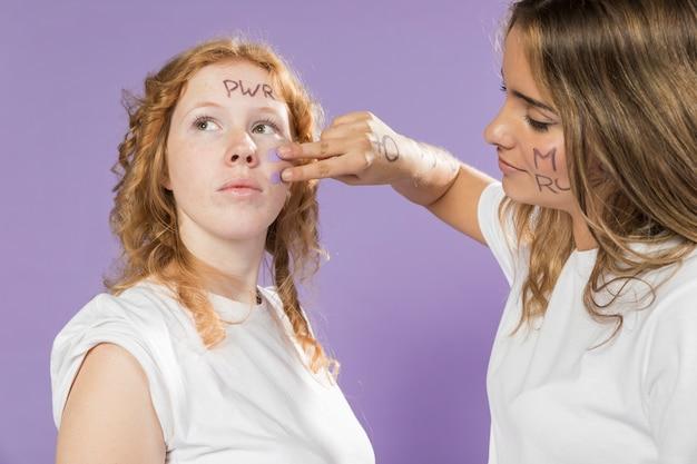 Nahaufnahmefrauen-malereifreundgesicht für protest Kostenlose Fotos