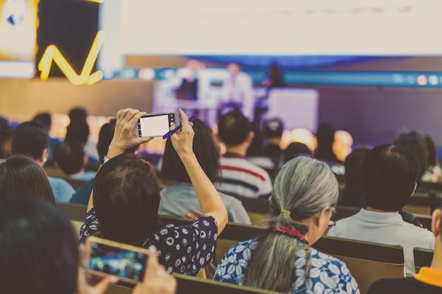 Nahaufnahmefrauen-publikumhand, die intelligenten handy für das nehmen des fotos oder das tun von live stre hält Premium Fotos