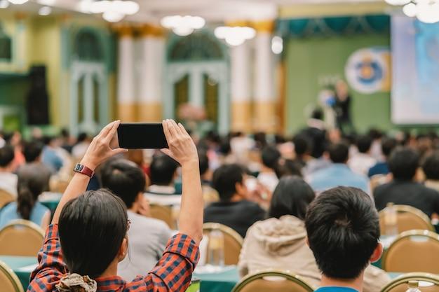 Nahaufnahmefrauen-zuschauerhand, die intelligenten handy für das nehmen des fotos oder das tun von live stre hält Premium Fotos