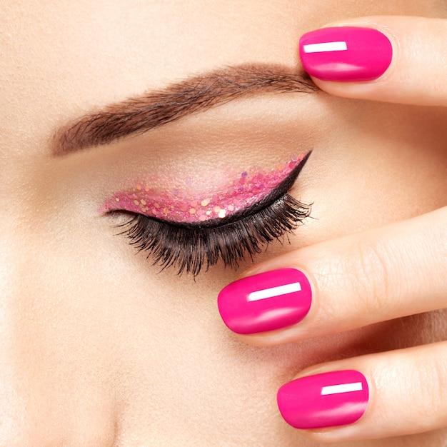 Nahaufnahmefrauengesicht mit rosa nägeln nahe augen. fingernägel mit rosa maniküre Kostenlose Fotos