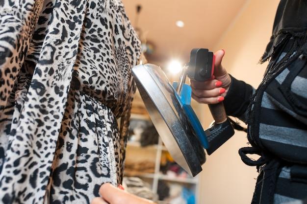 Nahaufnahmefrauenhand macht das kleid mit einem dampfbügeleisen auf einem mannequin glatt Premium Fotos