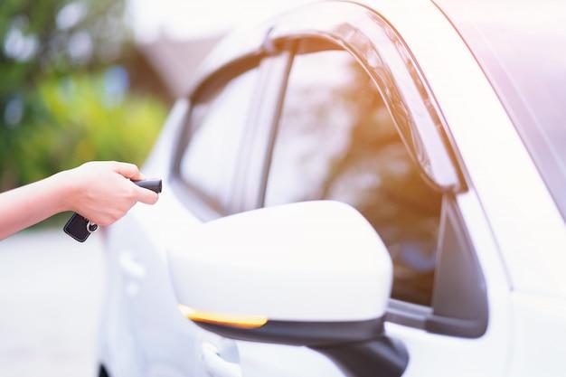 Nahaufnahmefrauenhand, welche die fernsteuerungsautowarnungssysteme hält Premium Fotos