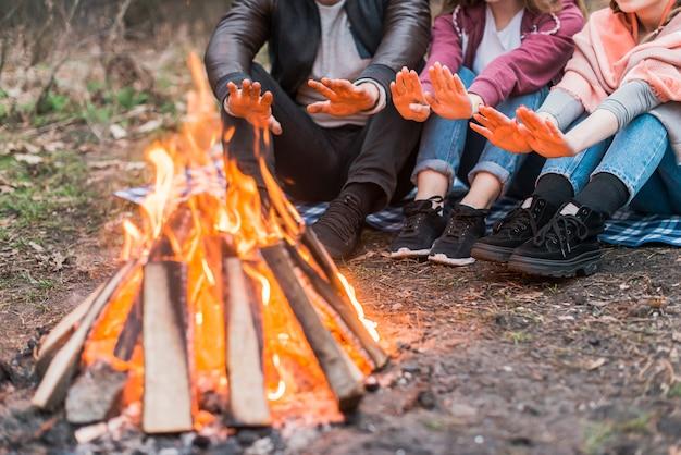 Nahaufnahmefreunde, die im feuerlager wärmen Premium Fotos