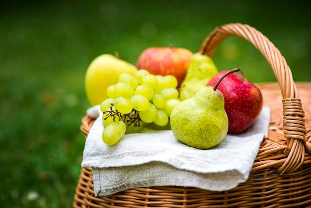 Nahaufnahmefrucht auf einem picknickkorb Kostenlose Fotos