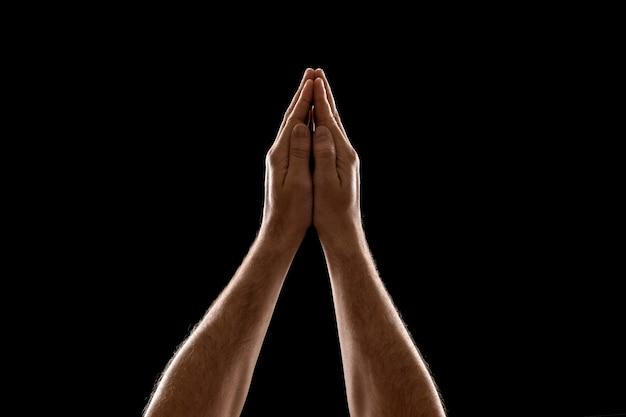 Nahaufnahmegebet des mannes handlokalisiert auf schwarzem hintergrund. Premium Fotos