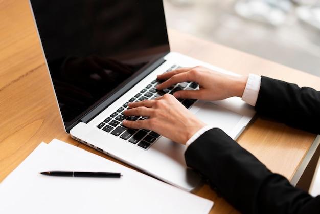 Nahaufnahmegeschäftsmann, der an einem laptop arbeitet Kostenlose Fotos