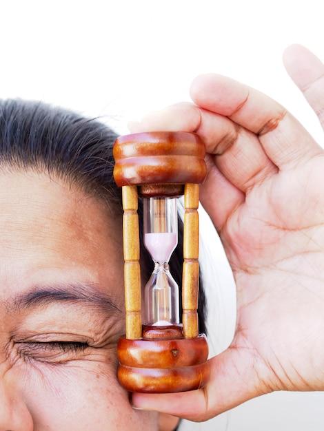 Nahaufnahmegesicht der asiatin mit der hand, die sanduhr, zeit hält, um haut und falten sich zu kümmern. Premium Fotos