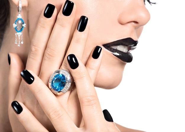 Nahaufnahmegesicht der jungen schönen frau mit schwarzer maniküre und hellem mode-make-up Kostenlose Fotos