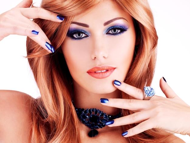 Nahaufnahmegesicht einer sinnlichen schönen frau mit blauen nägeln, blauem make-up und sexy roten lippen auf weißer wand Kostenlose Fotos