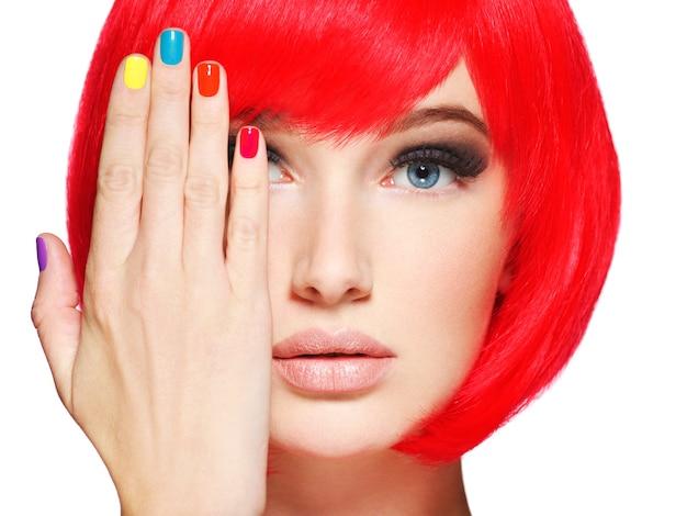 Nahaufnahmegesicht eines schönen mädchens mit hellen mehrfarbigen nägeln. Kostenlose Fotos