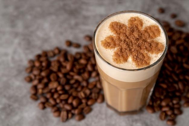 Nahaufnahmeglas milchkaffee mit gebratenen bohnen Kostenlose Fotos