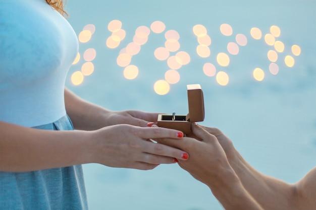 Nahaufnahmehände. der mann macht dem mädchen am abend in der sandwüste einen heiratsantrag Premium Fotos