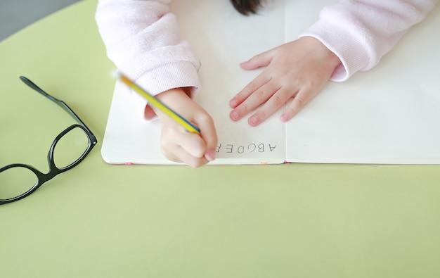 Nahaufnahmehände des kleinen kindes schreibt abc in ein buch oder in ein notizbuch mit bleistift auf tabelle. Premium Fotos