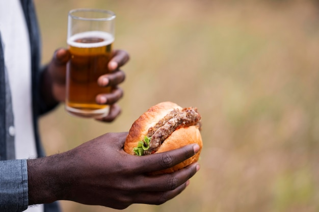 Nahaufnahmehände, die bier und burger halten Kostenlose Fotos