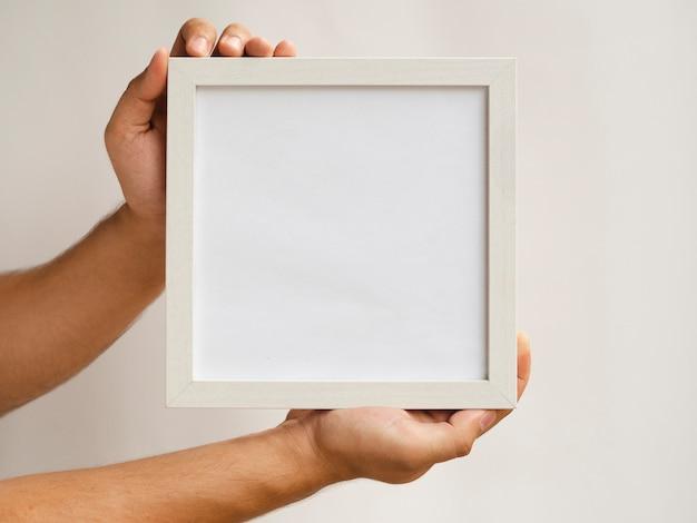 Nahaufnahmehände, die ein rahmenmodell halten Kostenlose Fotos