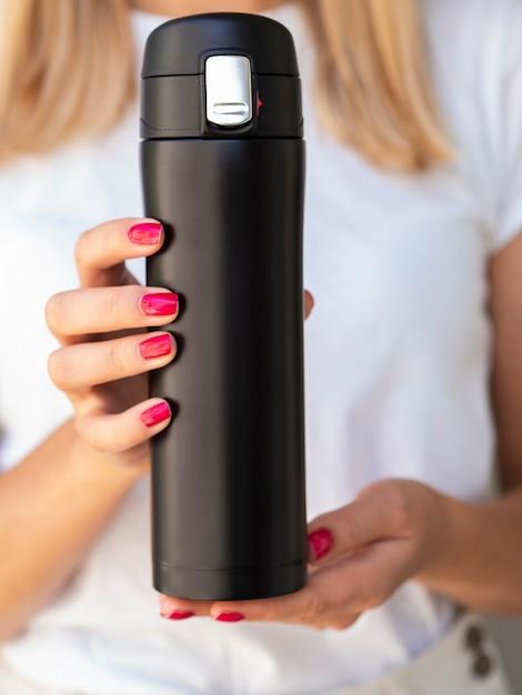 Nahaufnahmehände, die ein thermosflaschenmodell halten Kostenlose Fotos