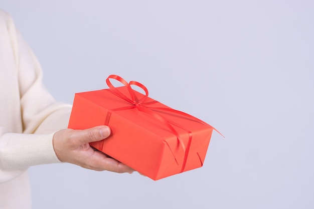 Nahaufnahmehände, die geschenkbox geben. frau liefert ein rotes paketgeschenk mit rotem band. geburtstag, boxing day oder weihnachten konzept. Premium Fotos