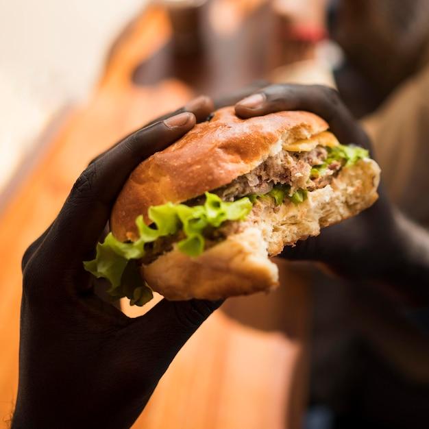 Nahaufnahmehände, die köstlichen burger halten Kostenlose Fotos