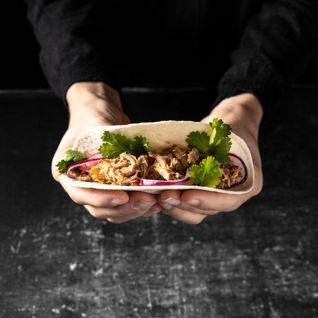 Nahaufnahmehände, die leckeren taco halten Kostenlose Fotos