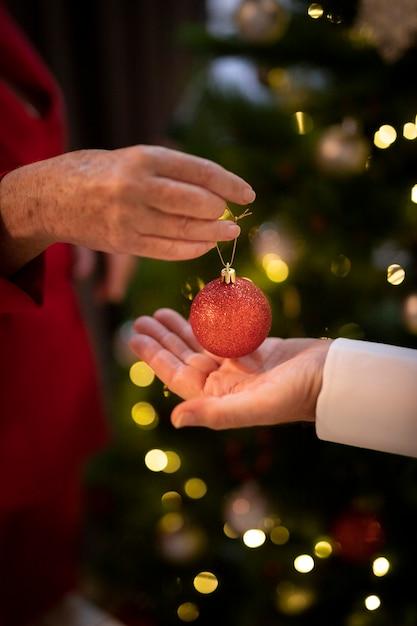 Nahaufnahmehände, die weihnachtsball halten Kostenlose Fotos
