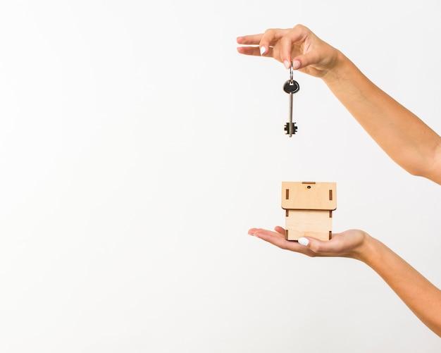 Nahaufnahmehände mit schlüssel und einem häuschen Kostenlose Fotos
