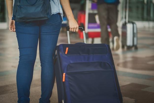 Nahaufnahmehand, die das gepäck über dem flugbrett für abfertigung am flug informat hält Premium Fotos