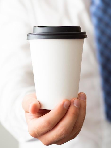 Nahaufnahmehand, die kaffeetassemodell hält Kostenlose Fotos