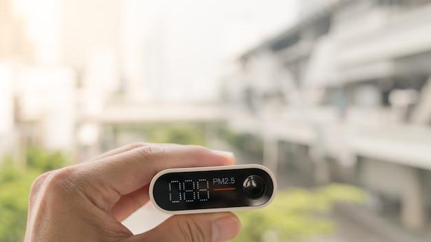 Nahaufnahmehand, die luftqualitätsüberwachung hält, um verschmutzungsgrad oder kleine partikel in der stadt zu erfassen Premium Fotos