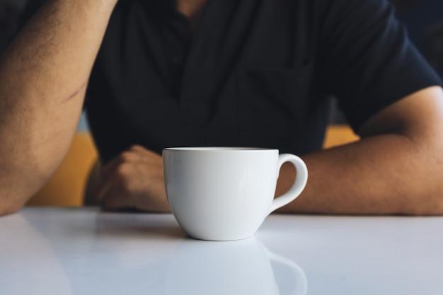 Nahaufnahmehand eines geschäftsmannes, der eine weiße tasse kaffee im raum hält Premium Fotos
