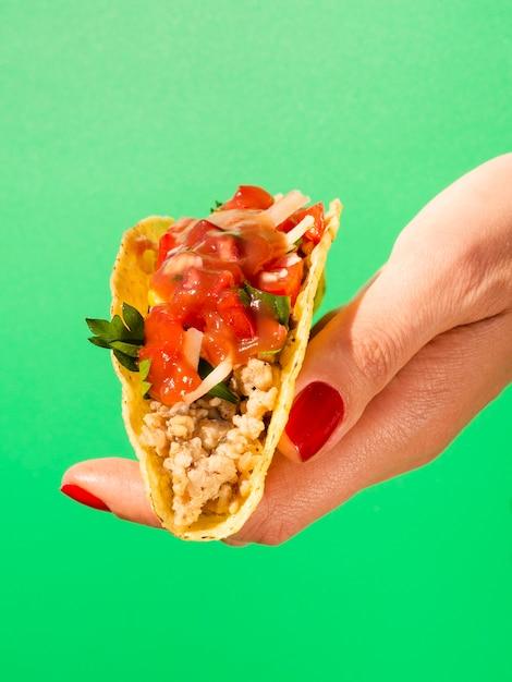 Nahaufnahmehand mit taco und grünem hintergrund Kostenlose Fotos