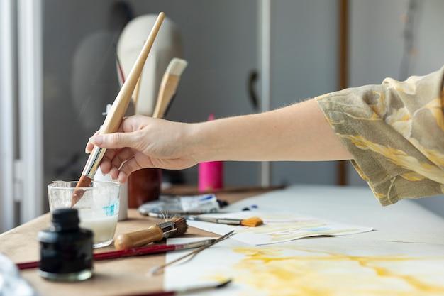 Nahaufnahmehand unter verwendung des aquarells für das malen Kostenlose Fotos