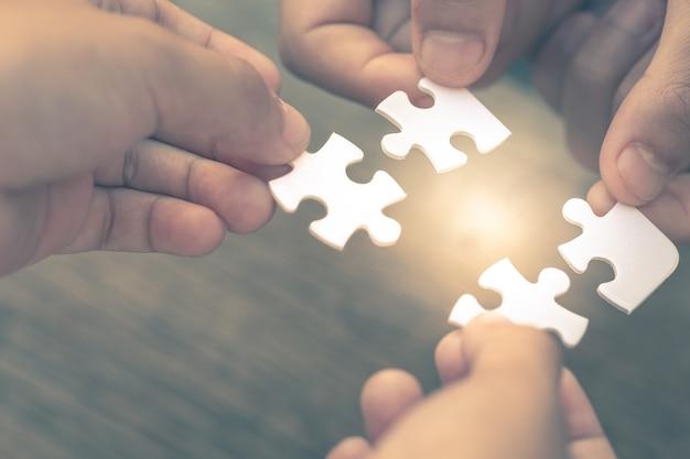 Nahaufnahmehand von verschiedenen leuten, die puzzle verbinden, das eine teamarbeit des geschäfts ist Premium Fotos